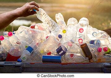 Hand holding recyclable plastic  bottle in garbage bin
