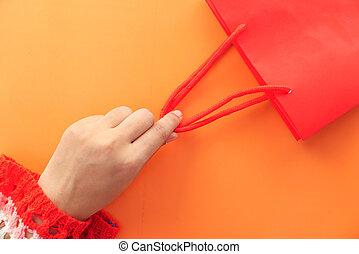 hand holding red color shopping bag on orange background
