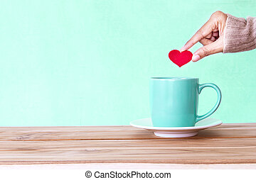 hand holding red heart shape put into a Coffee cup mug on wooden table , Romance and love valentines day background . Happy and relax concept