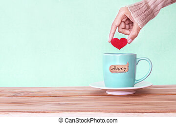 hand holding red heart shape put into a Coffee cup mug with happy word tag on wooden table , Romance and love valentines day background . Happy and relax concept