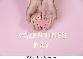 hand holding red heart with valentines day word on pink background.