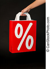 hand holding red shopping bag with percent sign