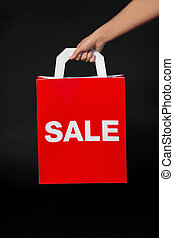 hand holding red shopping bag with sale word