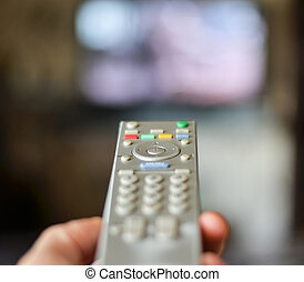 Hand holding remote controller with tv in the background