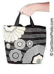 Hand holding reusable shopping bag
