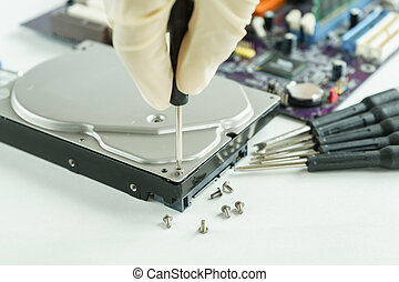 hand holding screwdriver to open hard disk drive