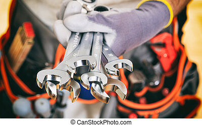 Hand holding set of spanners