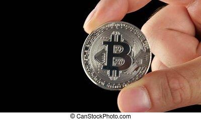 Hand holding silver Bitcoin virtual money.