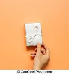 Hand holding silver gift box on orange background. top view, copy space