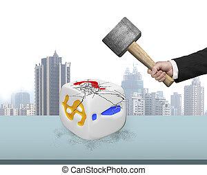 hand holding sledgehammer hitting white dice on desk