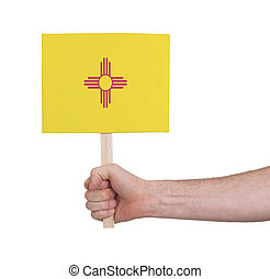 Hand holding small card, isolated on white - Flag of New Mexico