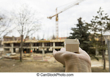 Hand holding small house model in front of construction site, real estate concept