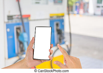 hand holding smart phone and gas station in background.