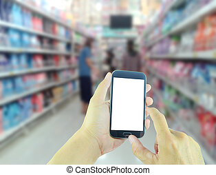 Hand holding smart phone with blur supermarket background
