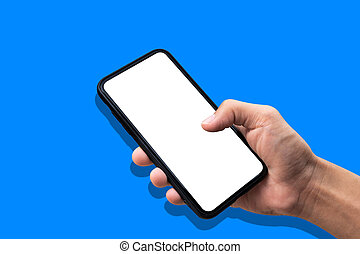 Hand holding smartphone on blue background.