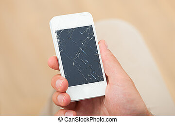 Cropped image of man's hand holding smartphone with broken screen at home