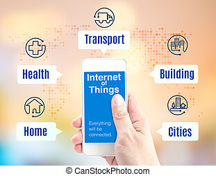 Hand holding smartphone with Internet of things (IoT) word and application icon on blur background, Digital Marketing concept