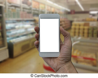 Hand holding smartphone with white blank screen over blurred supermarket and retail store in shopping mall interior background for product display montage