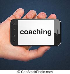 Hand holding smartphone with word coaching on display. Generic mobile smart phone in hand on dark blue background.