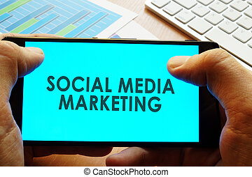 Hand holding smartphone with words social media marketing.