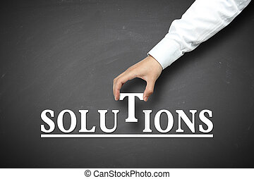 Solution concept with businessman hand holding against blackboard background.