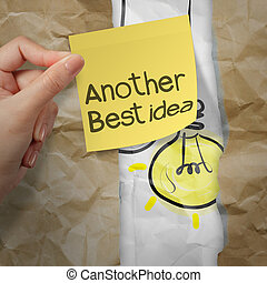 hand holding sticky note with another idea light bulb on crumpled paper as creative concept