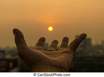Hand holding sunset and city of background