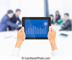 hand holding tablet PC with  higher financial graph on business people background