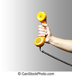 hand holding telephone - hand holding a yellow vintage...