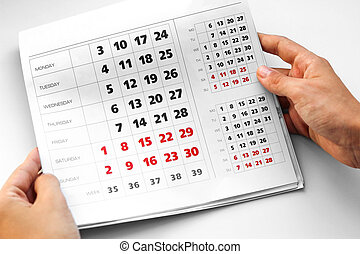 Hand holding the calendar. White calendar. Weekends are highlighted in red. Close up