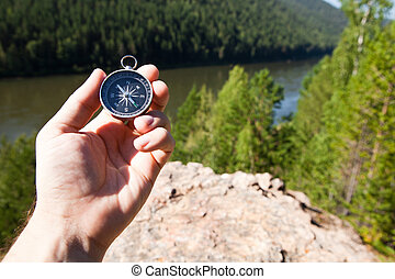 Hand holding the compass. Hike concept.