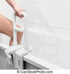 hand holding the handrail in the bathroom - hand holding the...