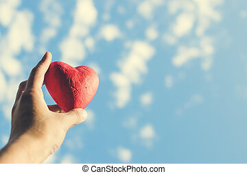 Hand holding the red decorative heart against the blue sky.