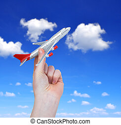 Hand holding the toy plane against cloudy sky