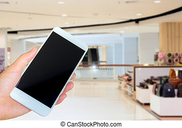 hand holding the white smartphone on blurred background