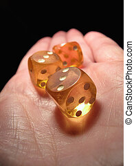 Hand holding three old dice on a black background