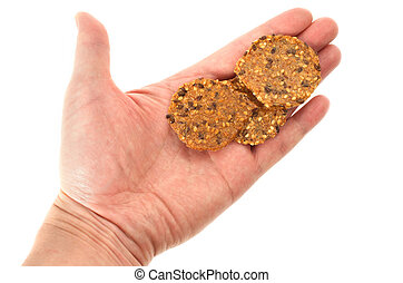 Hand holding three sesame crackers on white background