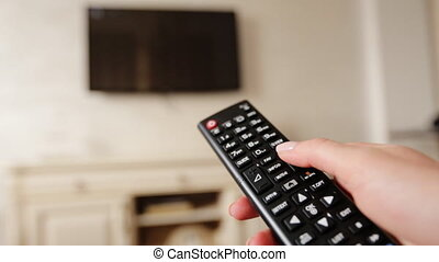 Hand holding TV remote control and changing channels on television.