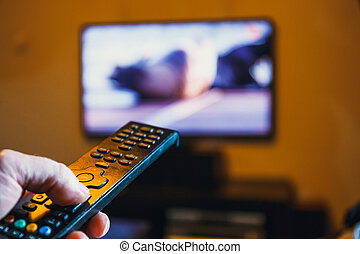 Hand holding TV remote control and presses the button