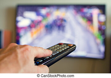 Hand holding TV remote control with a television in the...