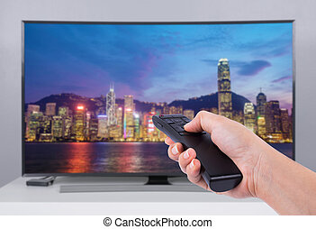 Hand holding TV remote control with a television and city screen
