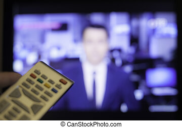 Hand holding TV remote with a television in the background