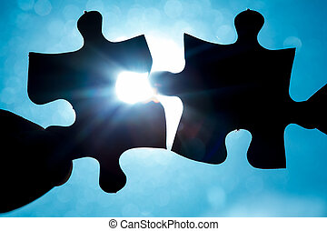 Hand holding two jigsaw pieces