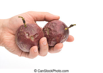 hand holding two passion fruits on a white background