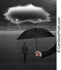 Hand holding umbrella protecting businessman from dark cloud rai
