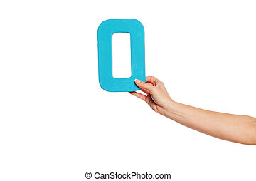 hand holding up the letter O from the right