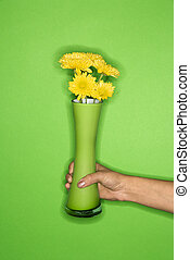 Hand holding vase with flowers.