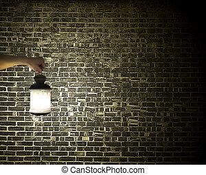Hand holding vintage lamp illuminating dark brick wall