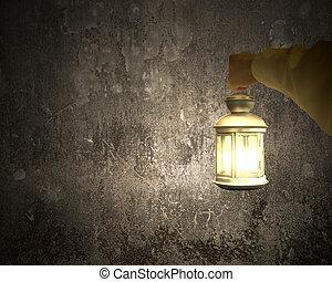 Hand holding vintage lamp illuminating dark concrete wall