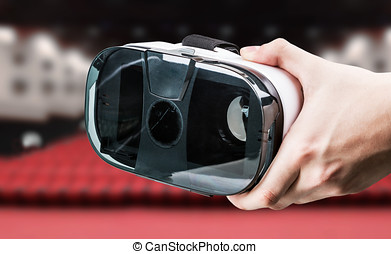 Hand holding virtual reality glasses in the cinema